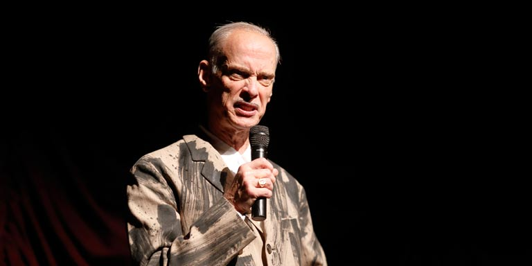 John Waters speaking on a microphone on stage